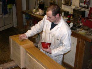 man polishing clock case